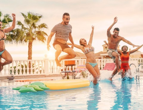 Group of happy friends drinking jumping in pool sunset party outdoor - Young diverse culture people having fun in tropical vacation - Holiday, youth and friendship concept - Main focus on left man